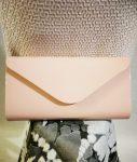 Magasfényű, púder rózsaszín színű, egy rekeszes, patentos záródású, hosszú pánttal is használható alkalmi kézi táska